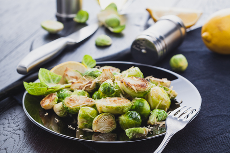 Roasted Brussel Sprouts with Parmesan cheese, lemon, Salt, Pepper on a black table.