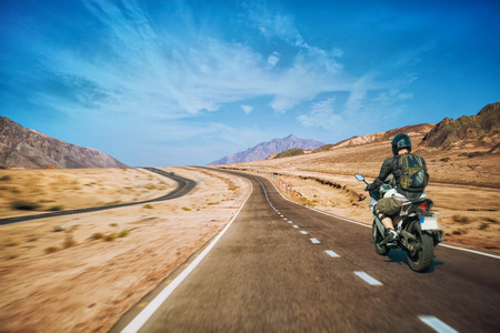 Motorcyclist rushes along the picturesque desert mountain highway