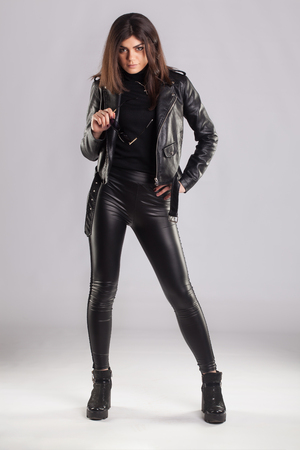 Young brunette lady in black leather jacket and pants posing on grey background