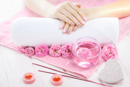 Beautiful pink manicure with decor, tea rose, towel and candle on the white wooden table. spa