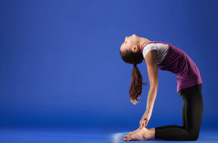 young woman doing yoga practice isolated on blue background.