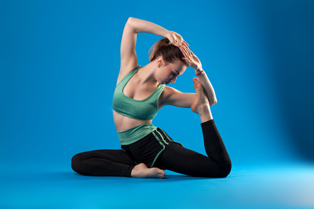 young beautiful dancer posing on isolated blue studio background Stockfoto