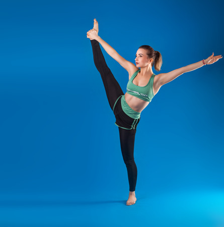 young beautiful dancer posing on isolated blue studio background Фото со стока