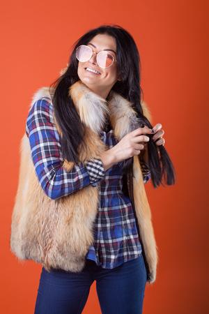 pretty woman model pose wear plaid shirt and fur vest on the orange studio background