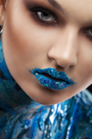 Creative turquoise makeup and body art on a blue background. Imagens