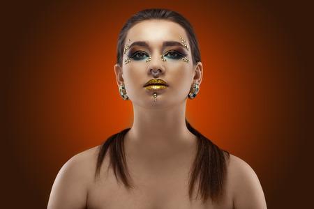 Porträt eines Mädchens. luxuriöses glänzendes Make-up auf dunklem Hintergrund Standard-Bild