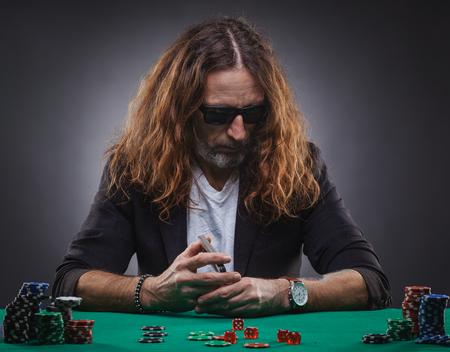 Langhaariger gutaussehender Mann, der Poker in einem Casino spielt.
