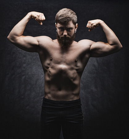 Young strong man bodybuilder on the black background. Stock Photo