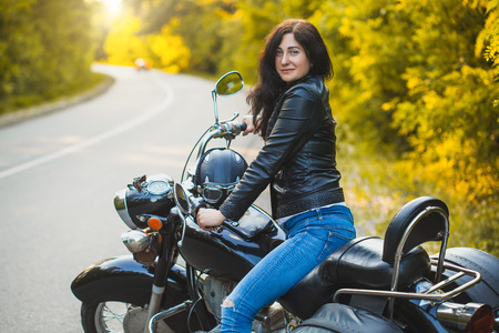 attractive brunette motorcyclist sits on a motorcycle.