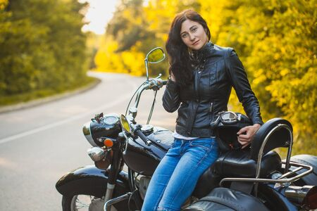 attractive brunette motorcyclist sits on a motorcycle. Stok Fotoğraf