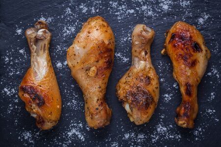 Roasted chicken legs on the black background. Top view.