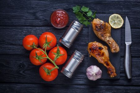 chicken legs with tomatoes, lemon, parsley and ketchup on a black slate board Stok Fotoğraf