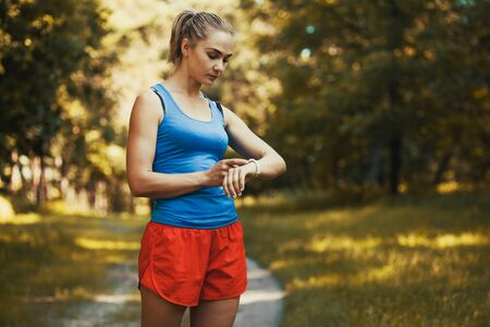 Pretty woman athlete doing exercises before jogging through the woods