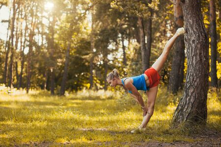 young woman is doing warming up before running in the forest on a beautiful summer day Stok Fotoğraf