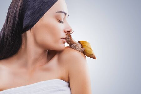 Beautiful young woman kissing giant Achatina snail on light background