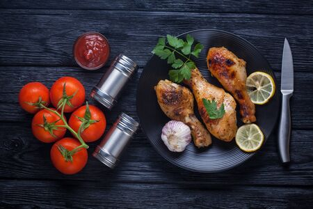 chicken legs with tomatoes, lemon, parsley and ketchup on a black plate