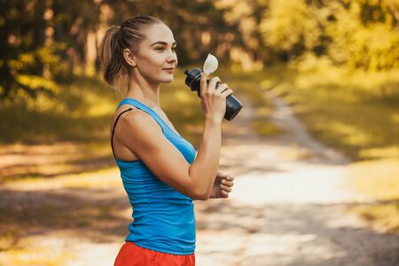 woman athlete takes a break, she drinking Stok Fotoğraf