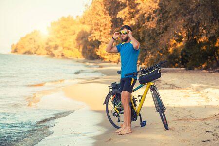 bearded man cyclist rides along the sandy beach on a mountain bike.