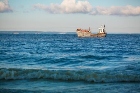 old fishing boat going on the sea waves