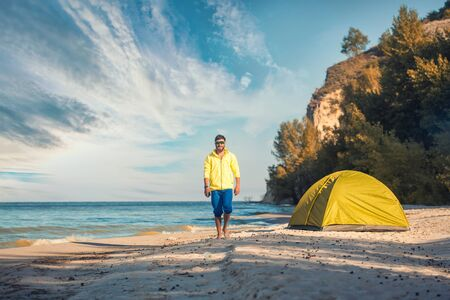 bearded man resting with a tent on a sandy beach. Stok Fotoğraf