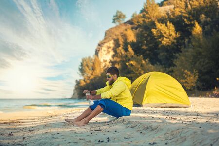 bearded man resting with a tent on a sandy beach. Imagens