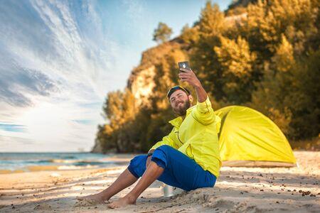 bearded man makes a selfie with a tent on a sandy beach.