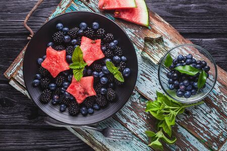 Frock blueberry, blackberry, watermelon and mint salad on an old wooden table Stok Fotoğraf