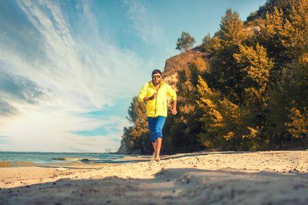 bearded athlete runs along the sandy beach.