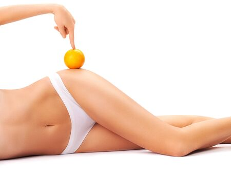 beautiful female body with an orange isolated on a white background. Archivio Fotografico - 133855075