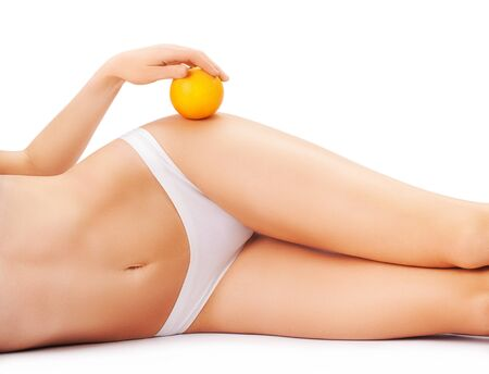 beautiful female body with an orange isolated on a white background. Archivio Fotografico - 133855079