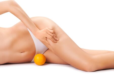 beautiful female body with an orange isolated on a white background. 스톡 콘텐츠