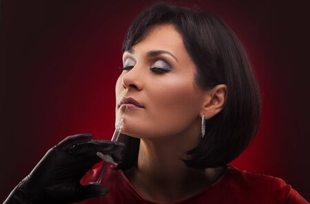 woman beautician with syringe on the red background Archivio Fotografico - 133855104