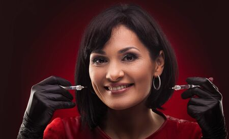 woman beautician with syringe on the red background Archivio Fotografico - 133855107