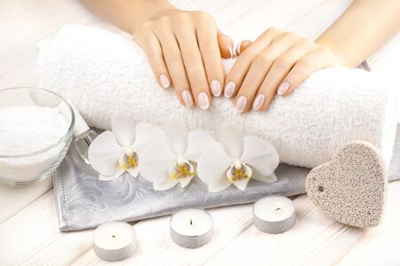 beautiful french manicure with orchid, candle and towel on the white wooden table.