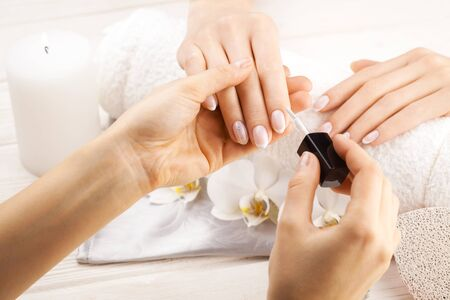 beautiful french manicure with orchid, candle and towel on the white wooden table. manicurist hands