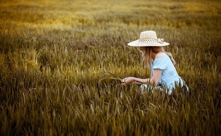 Young woman in hat sits on the wheat field with sunset on the background Banque d'images