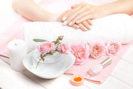 schöne französische Maniküre mit Rosen, Kerze und Handtuch auf dem weißen Holztisch.
