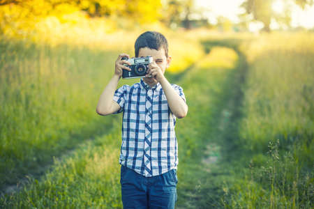 Beautiful smiling kid boy holding a retro camera in the park