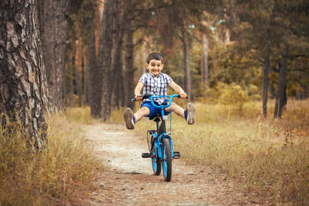 Happy kid cyclist rides in the forest on a bike. Banque d'images