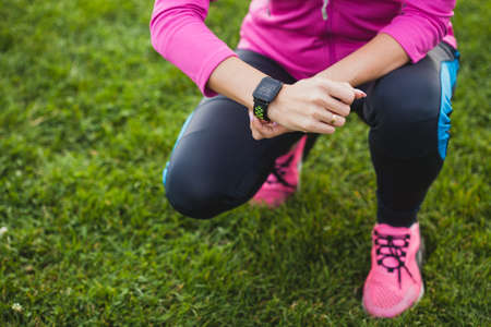 woman runner measures heart rate while jogging using smart watch Stock Photo