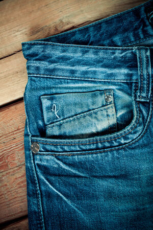 Blue jeans pocket  on wooden background photo
