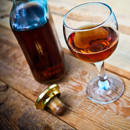 drunks: bottle and glass of cognac with ice on a wooden background