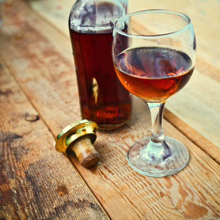bottle and glass of cognac with ice on a wooden background photo