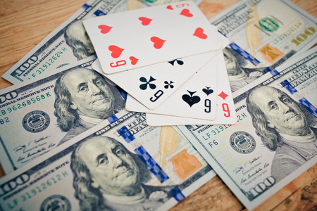 Four aces poker playing cards among U.S. dollar banknotes photo