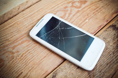 damaged: Broken glass of smart phone on the wood
