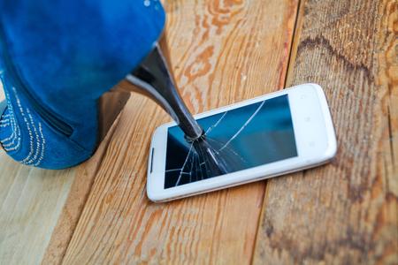 crushing: High heel shoe crushing a mobile phone.