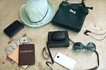 student travel: Outfit of traveler. Different objects : leather bag, camera, smartphone, glasses, hat,passport