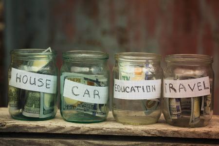 Glazen potten met dollars en tekst: huis, auto, reizen, onderwijs