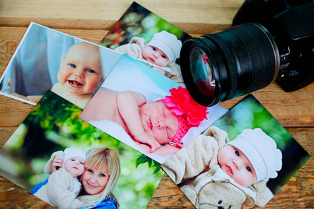 Childrens photos and camera on a wooden background.
