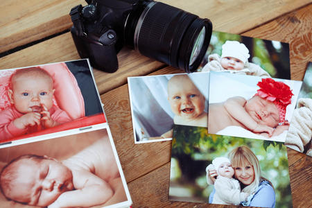 Children's photos and camera on a wooden background. Stock Photo